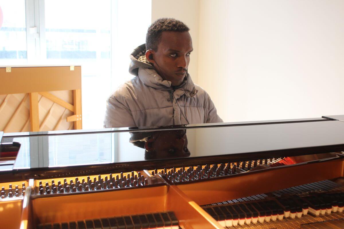 Der sehbeinträchtigte äthiopische Projektteilnehmer Habtamu Shiawul spielt auf einem Klavier. Foto: Nora Gohlke