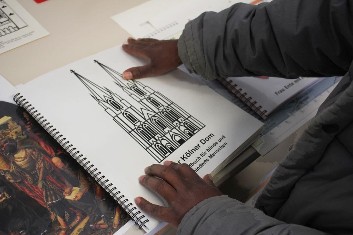 Auf einer taktilen Buchseite ist der Kölner Dom abgebildet. Foto: Nora Gohlke