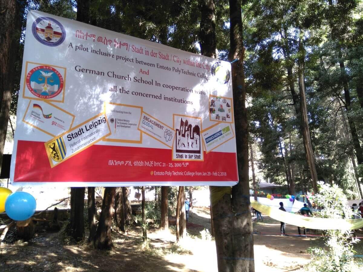 Ein Banner weist auf das inklusive Ferienspiel Stadt in der Stadt in Addis Abeba hin