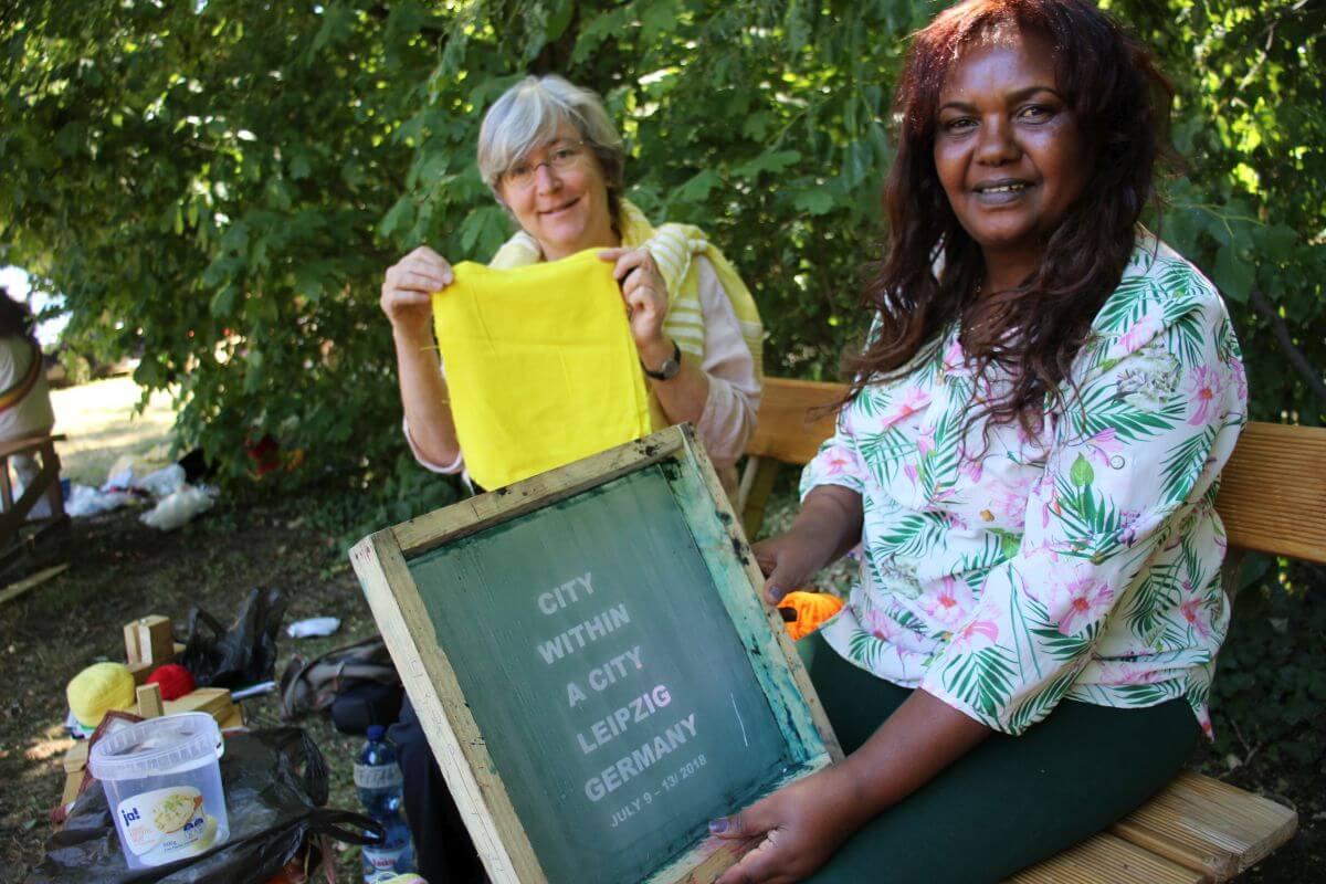 Zwei Teilnehmerinnen aus Äthiopien zeigen ein Schild mit der Aufschrift City within the City Leipzig Deutschland und ein Tuch.