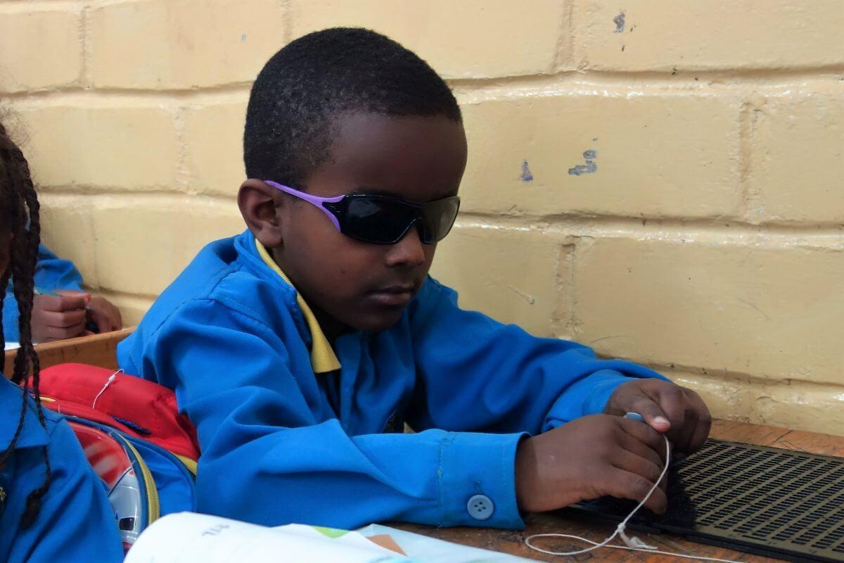 Ein sehbeinträchtigter Junge in der German Church School arbeitet mit speziellem Material in der Schulbank.